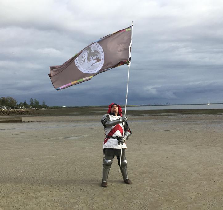 Sir Ashley Dean holds the flag aloft